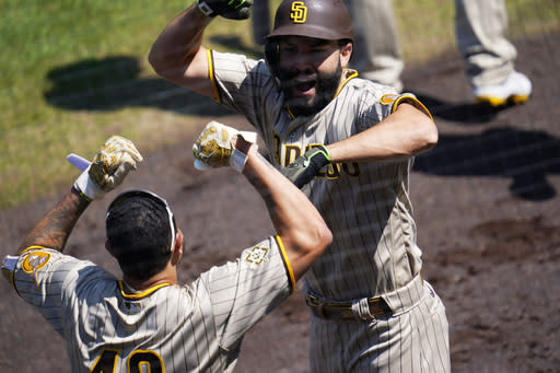 San Diego Padres' Eric Hosmer, back, celebrates hitting a three-run home run with Manny Machado in the first inning of a baseball game against the Colorado Rockies Sunday, Aug. 30, 2020, in Denver.(AP Photo/David Zalubowski)