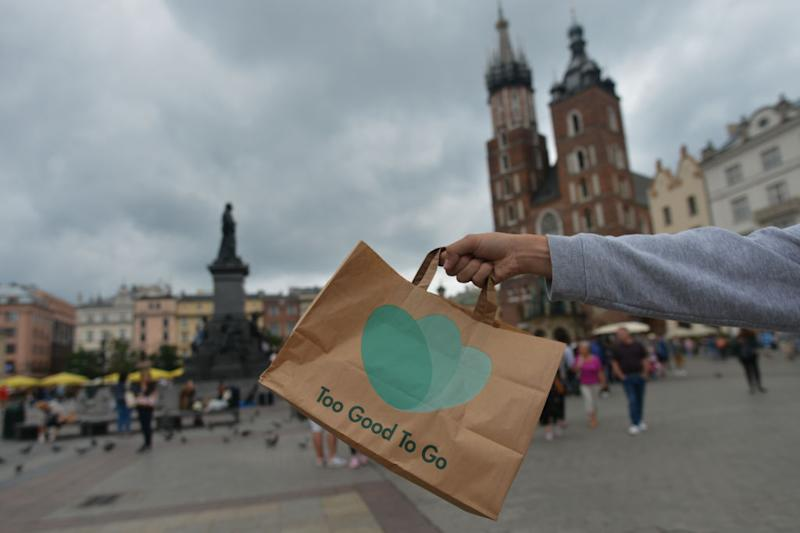 A man carries Too Good To Go bag with food in Krakow's Main Market Square. Too Good To Go allows local food stores, cafes and restaurants to sign up and post the left-over meals that they have at the end of the day and the discounted price they want for them. Too Good To Go (TGTG) is world's number 1 app for fighting food waste. On Wednesday, August 11, 2019, in Krakow, Poland. (Photo by Artur Widak/NurPhoto)