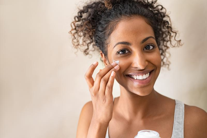 Smiling african girl with curly hair applying facial moisturizer while holding jar and looking at camera. Portrait of young black woman applying cream on her face isolated on beige background. Close up of happy attractive beauty woman caring of her skin standing on light brown wall with copy space.
