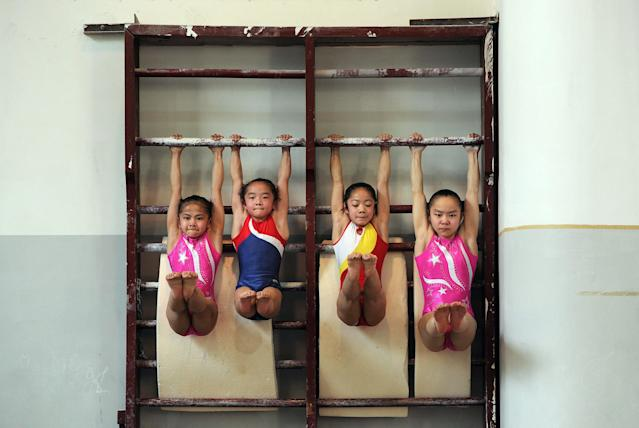 In a photograph taken on April 7, 2012, young Chinese gymnasts train at a special sport school in Hefei, east China's Anhui province. Potential gymnasts embark on a gruelling schedule which aims to create champions, as schooling and family take a back seat to eight hours of training six days a week, while quitting the rigid system that demands total dedication, and in which the state invests millions of dollars to develop its athletes, is rarely an option. CHINA OUT AFP PHOTO (Photo credit should read AFP/AFP/Getty Images)