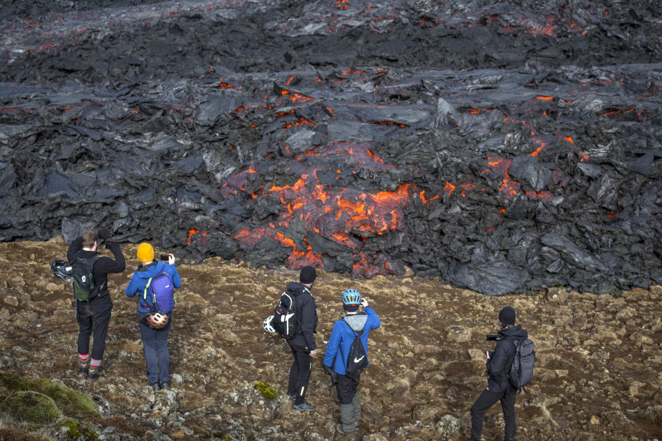 People watch and take photos as lava flows from an eruption of a volcano on the Reykjanes Peninsula in southwestern Iceland on Tuesday, March 23, 2021. Iceland's latest volcano eruption is quickly attracting crowds of people hoping to get close to the gentle lava flows. The eruption in Geldingadalur, near Iceland's capital Reykjavik, is not seen as a threat to nearby towns and the slow flows mean people can get close to action without too much harm. (AP Photo/Marco Di Marco)