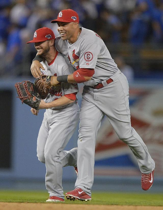 St. Louis Cardinals' Shane Robinson and Carlos Beltran, right, celebrate after Game 4 of the National League baseball championship series against the Los Angeles Dodgers Tuesday, Oct. 15, 2013, in Los Angeles. The Cardinals won 4-2 to take a 3-1 lead in the series. (AP Photo/Mark J. Terrill)