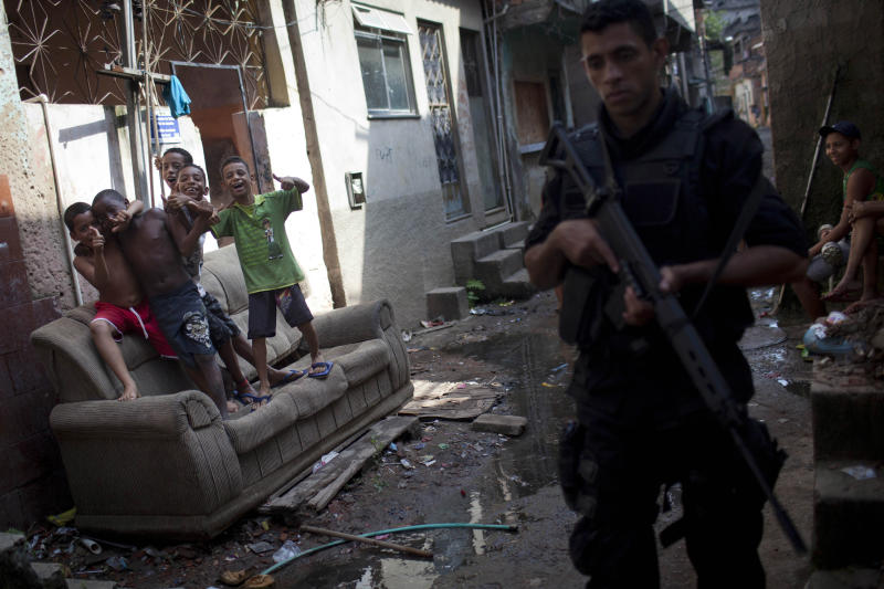 In this photo taken April 11, 2012, police from the Special Operations Battalion (BOPE) patrol as children joke in the Manguinhos slum in Rio de Janeiro, Brazil. Setbacks in a security program meant to take back territory from the drug trade have shown the immense challenge of pacifying the city's violent slums and raised questions about the state's ability to keep the peace as Rio prepares to take the world stage not just for the Olympics but the 2014 World Cup, which will host its headline events in Rio. (AP Photo/Felipe Dana)