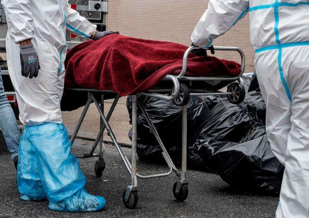 PHOTO: In this file photo taken on April 30, 2020, people in hazmat suits transport a deceased person on a stretcher outside a funeral home in the New York City borough of Brooklyn on April 30, 2020. (Johannes Eisele/AFP via Getty Images)
