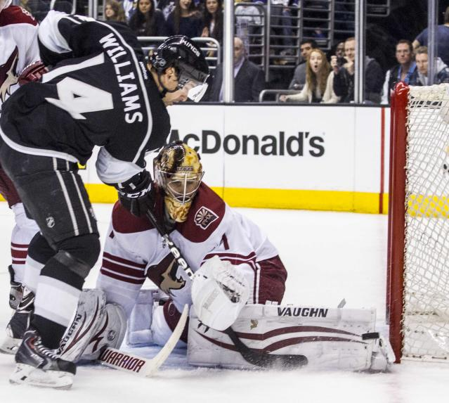 Phoenix Coyotes goalie Thomas Greiss (1) of Germany, makes a save shot by Los Angeles Kings forward Justin Williams (14) during the second period of an NHL hockey game, Wednesday, April 2, 2014, in Los Angeles. (AP Photo/Ringo H.W. Chiu)