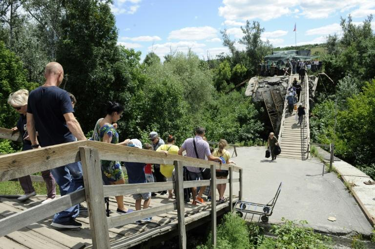 Those wanting to cross the bridge at Stanytsya Luganska have to walk the kilometre to the other side, while elderly people and those with disabilities have to pay to be taken in a wheelchair (AFP Photo/Evgeniya MAKSYMOVA)