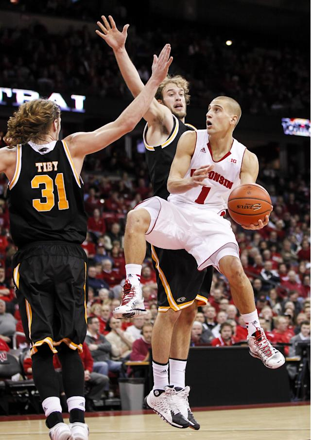 Wisconsin's Ben Brust (1) shoots against Milwuakee's Matt Tiby (31) and Kyle Kelm during the second half of an NCAA college basketball game on Wednesday, Dec. 11, 2013, in Madison, Wis. Wisconsin won 78-52. (AP Photo/Andy Manis)