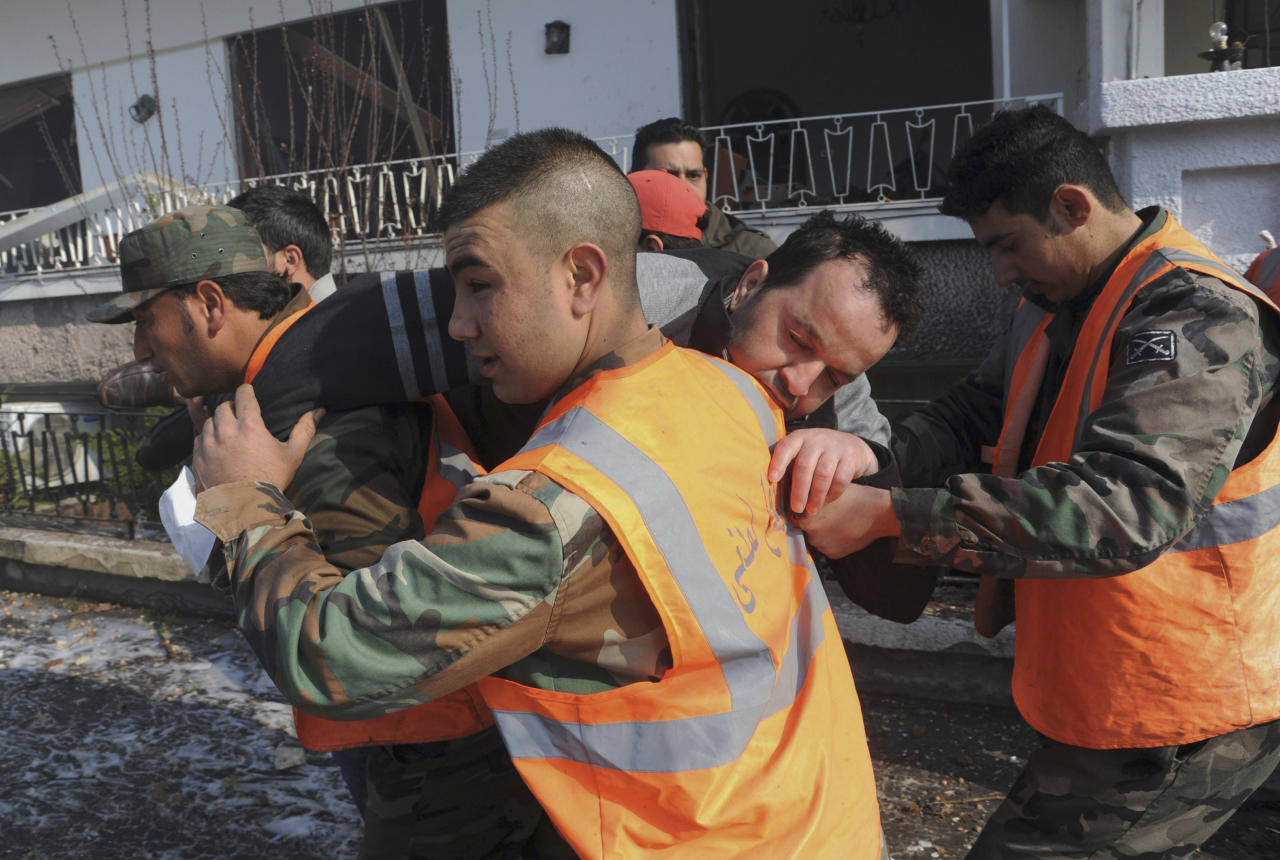 In this photo released by the Syrian official news agency SANA, Syrian army soldiers carry an injured man at the scene of the intelligence department, which was attacked by one of two explosions, in Damascus, Syria, on Saturday, March 17, 2012. Twin bombings struck government targets in the Syrian capital early Saturday, killing security forces and civilians and leaving pools of blood and carnage in the streets, according to state-run television. (AP Photo/SANA)
