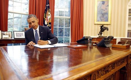 Obama signs into law S. 517, Unlocking Consumer Choice and Wireless Competition Act, at the White House in Washington
