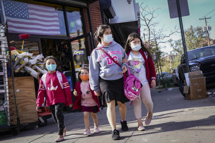 FILE- In this Oct. 15, 2020 file photo, pedestrians in masks pass a store in the Far Rockaway neighborhood in the Queens borough of New York, as government restrictions on business activity limit operations due to an increase of COVID-19 cases in the area. On Friday, Nov. 6, 2020, N.Y. Gov. Andrew Cuomo said that restrictions in some New York City pandemic hot spots will be rolled back, even as the state plans to combat flare-ups in and around upstate New York's largest cities. (AP Photo/John Minchillo, File)