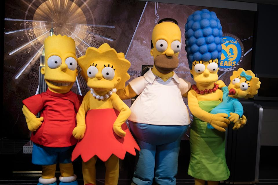 """NEW YORK, NY - DECEMBER 17:  (L-R) Bart Simpson, Lisa Simpson, Homer Simpson, Marge Simpson and Maggie Simpson visit The Empire State Building to celebrate the 30th anniversary of """"The Simpsons"""" at The Empire State Building on December 17, 2018 in New York City.  (Photo by Noam Galai/Getty Images)"""