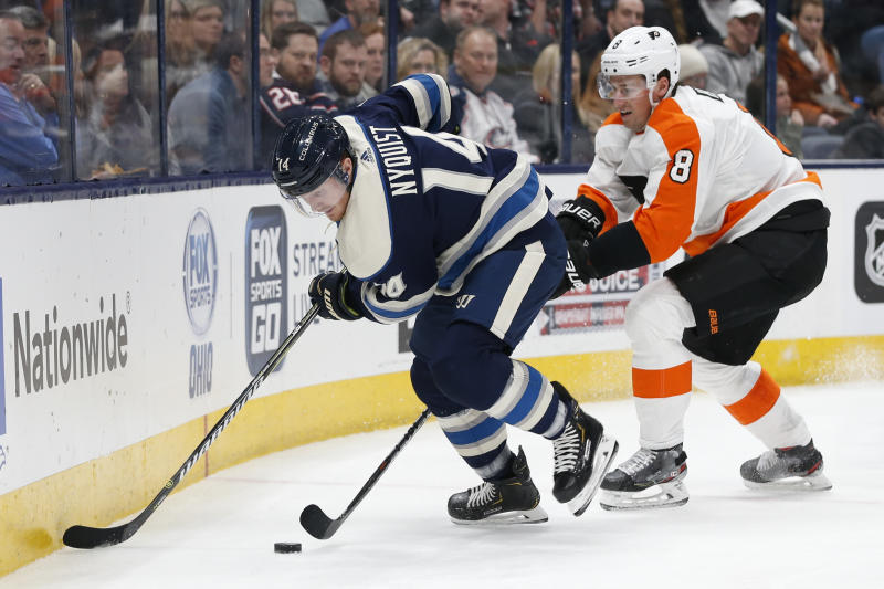 Columbus Blue Jackets' Gustav Nyquist, left, of Sweden, tries to control the puck against Philadelphia Flyers' Robert Hagg, also of Sweden, during the second period of an NHL hockey game Thursday, Feb. 20, 2020, in Columbus, Ohio. (AP Photo/Jay LaPrete)