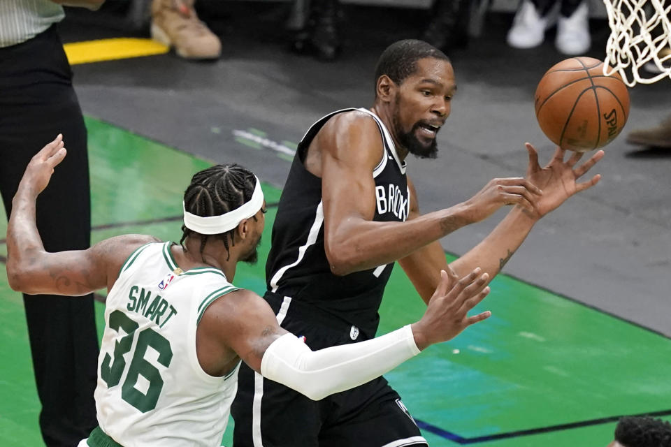 Brooklyn Nets forward Kevin Durant, right, is fouled by Boston Celtics guard Marcus Smart, left, as he goes to the hoop in the second half of Game 4 during an NBA basketball first-round playoff series, Sunday, May 30, 2021, in Boston. (AP Photo/Elise Amendola)