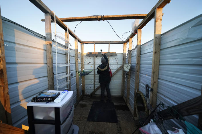 CORRECTS SPELLING TO CRISTIN, INSTEAD OF CRISTEN - Cristin Trahan looks at a new shower head and water heater, where she will take a hot shower for the first time since Hurricanes Laura and Delta, in a makeshift shower stall, where she now lives in a tent with her husband where their destroyed home once stood, in Lake Charles, La., Friday, Dec. 4, 2020. (AP Photo/Gerald Herbert)