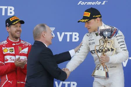 Formula One - F1 - Russian Grand Prix - Sochi, Russia - 30/04/17 - Russian President Vladimir Putin congratulates winner and Mercedes Formula One driver Valtteri Bottas of Finland as second-placed Ferrari Formula One driver Sebastian Vettel of Germany stands nearby on the podium. REUTERS/Maxim Shemetov
