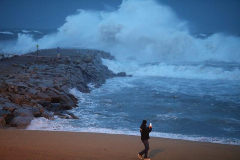 """Man takes pictures of the storm """"Gloria"""" on Barceloneta beach, in Barcelona"""