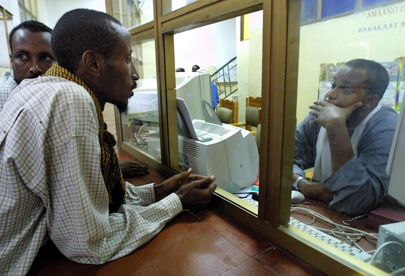 File photo shows an employee of Barakaat Bank of Somalia listening to a customer who was told that he cannot receive his money because the bank accounts were frozen by the US, in Mogadishu on November 10, 2001