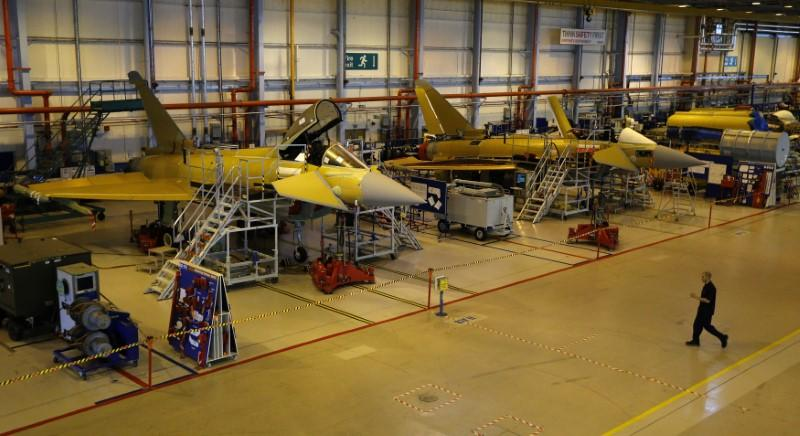 A worker crosses the floor of the Eurofighter Typhoon production line at BAE systems Warton plant near Preston