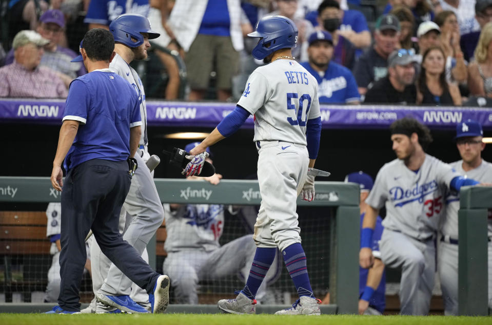 Los Angeles Dodgers' Mookie Betts (50) confers with Max Muncy as Betts leaves the game after doubling off Colorado Rockies relief pitcher Mychal Givens during the seventh inning of a baseball game Saturday, July 17, 2021, in Denver. (AP Photo/David Zalubowski)