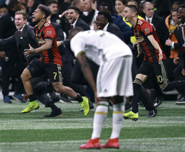 Portland Timbers defender Larrys Mabiala bends over in dejection as Atlanta United forward Josef Martinez (7) and midfielder Miguel Almiron (10) charge the field to celebrate winning the MLS Cup championship soccer game, Saturday, Dec. 8, 2018, in Atlanta. Atlanta won 2-0. (Curtis Compton/Atlanta Journal-Constitution via AP)