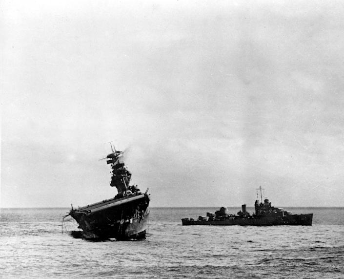 FILE - In this June 4, 1942 file photo provided by the U.S. Navy shows the USS Yorktown listing heavily to port after being struck by Japanese bombers and torpedo planes in the Battle of Midway. Researchers scouring the world's oceans for sunken World War II ships are honing in on debris fields deep in the Pacific. A research vessel called the Petrel is launching underwater robots about halfway between the U.S. and Japan in search of warships from the Battle of Midway. (AP Photo/U.S. Navy, File)