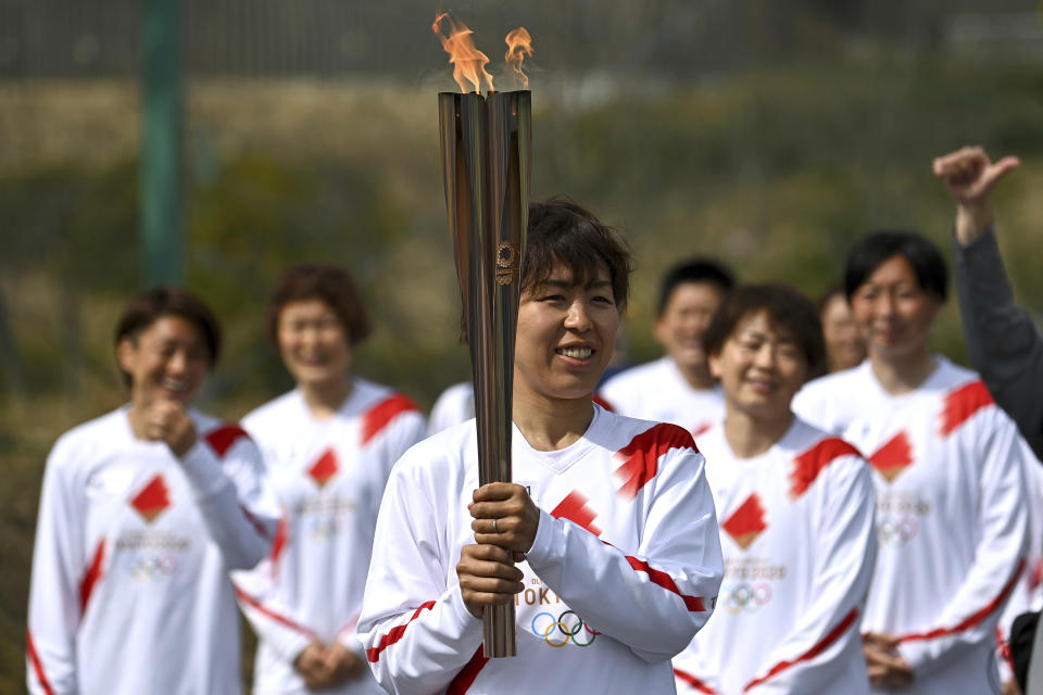 Japanese torchbearer Azusa Iwashimizu, center, a member of Japan women's national football team, arrives at a torch kiss point to pass on the flame during the torch relay grand start outside J-Village National Training Center in Naraha, Fukushima prefecture, northeastern Japan, Thursday, March 25, 2021. The torch relay for the postponed Tokyo Olympics began its 121-day journey across Japan on Thursday and is headed toward the opening ceremony in Tokyo on July 23. (Philip Fong/Pool Photo via AP)