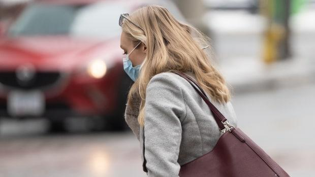 A woman wearing a mask walks near the intersection of Bank and Queen streets on Feb. 18, during the COVID-19 pandemic. (Brian Morris/CBC - image credit)