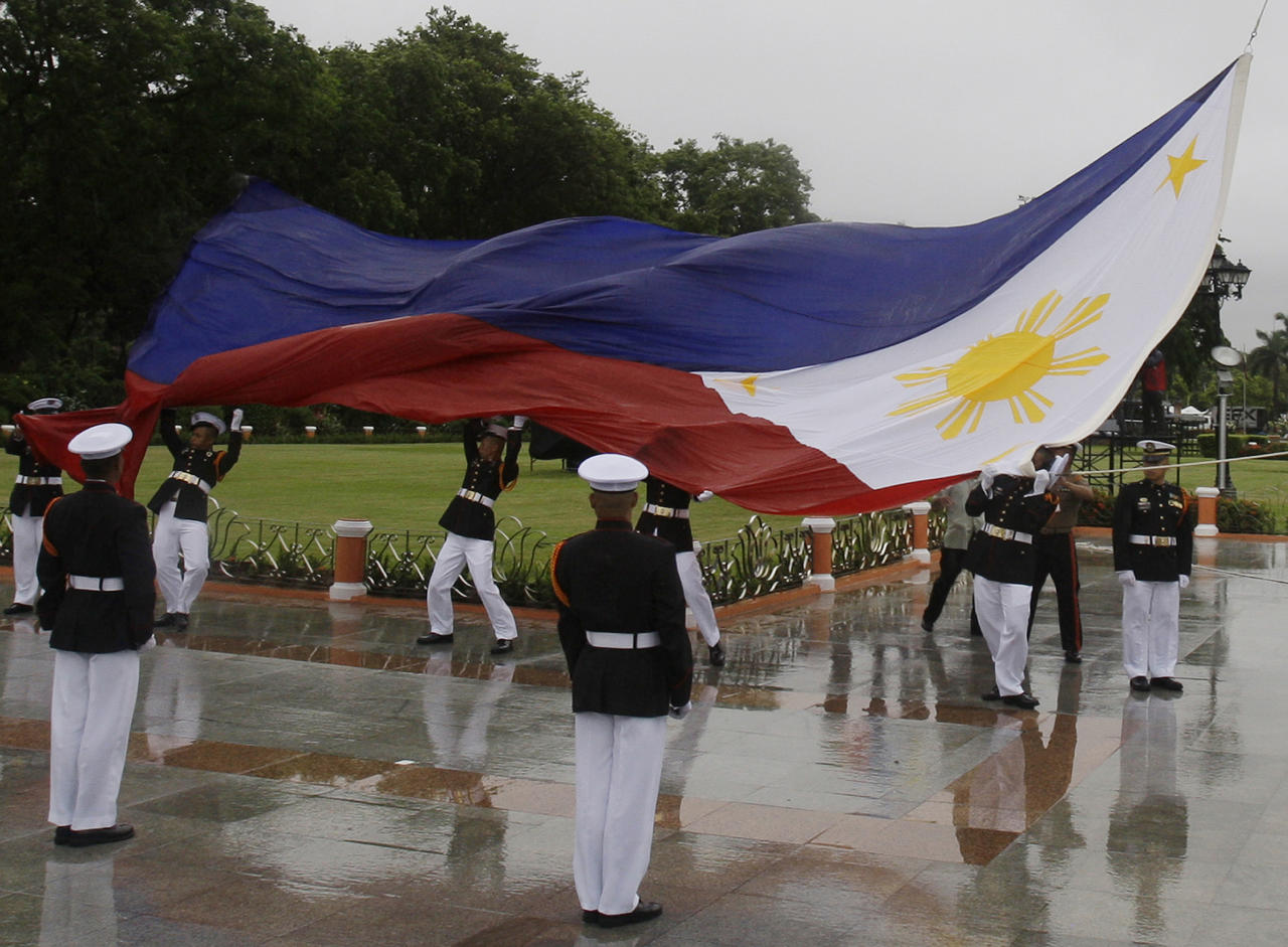 Filipino soldiers hold a large Philippine flag as it is blown by strong winds during flag raising ceremonies to celebrate the 150th birthday of Jose Rizal beside his monument in Manila, Philippines on Sunday June 19, 2011. Rizal is the country's national hero. (AP Photo/Aaron Favila)
