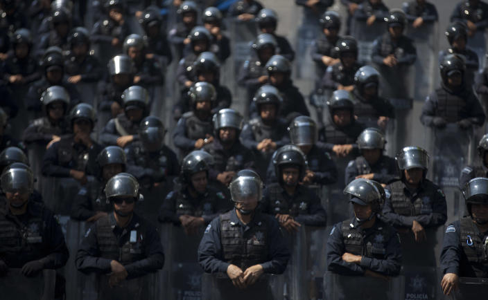 Mexico's Federal Police officers stand guard as public school teachers protest near Mexico's Interior Ministry in Mexico City, Thursday, April 4, 2013. Radical Mexican public school teachers are holding marches and blocking roads to battle a newly enacted education reform that would weaken union powers. (AP Photo/Alexandre Meneghini)