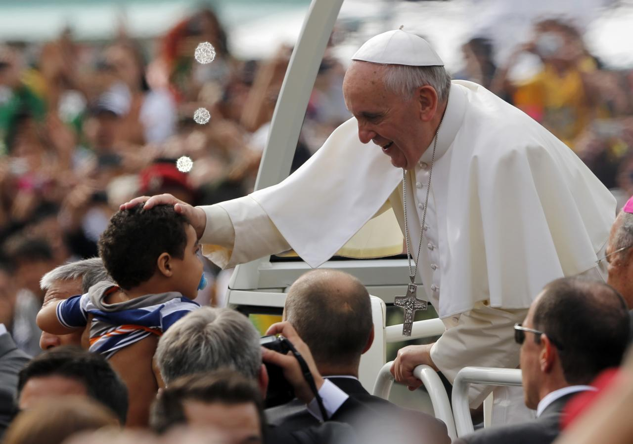 Pope Francis blesses a child as he rides on the popemobile to celebrate mass in Rio de Janeiro Sunday July 28, 2013. Hundreds of thousands of young people slept under chilly skies in the white sand of Copacabana awaiting Pope Francis' final Mass for World Youth Day.(AP Photo/Jorge Saenz)