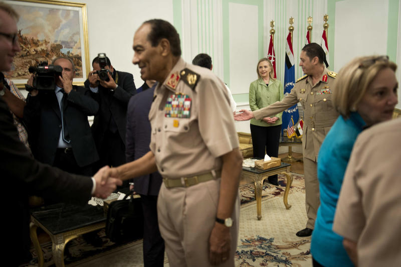 US Secretary of State Hillary Rodham Clinton, back center, watches as Field Marshal Hussein Tantawi, second left, greets members of the American delegation before a meeting at the Ministry of Defense July 15, 2012 in Cairo, Egypt. Clinton is holding talks with Egypt's top military leaders to press for the military to work with Egypt's new Islamist leaders on a full transition to civilian rule. (AP Photo/Brendan Smialowski, Pool)