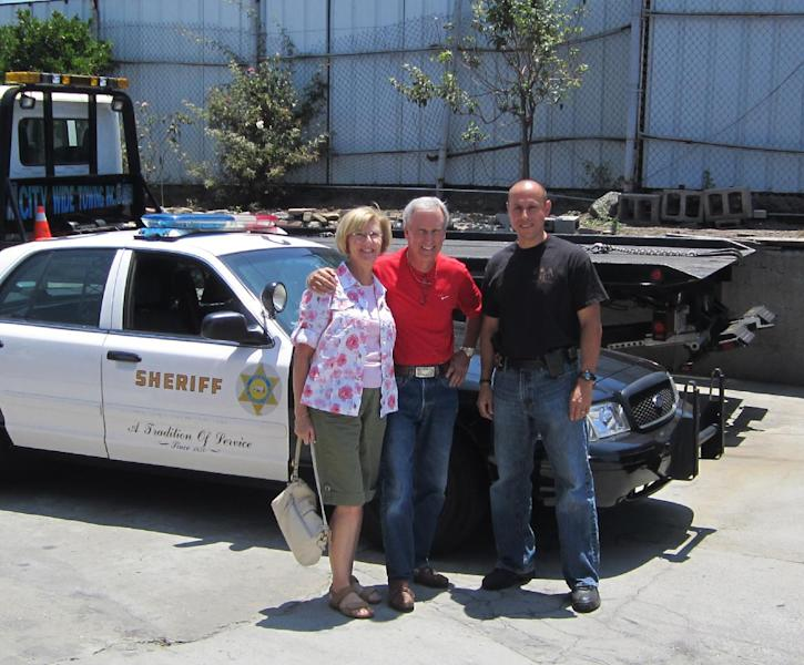 In this image provided by the Los Angeles County Sheriff's Department Bob Russell, center, and his wife standing next to Los Angeles County Sheriff's Department East LA Auto Theft Detective Carlos Ortega. Russell whose prized 1967 Austin Healy sports car was stolen 42 years ago, recovered the vehicle after spotting it on eBay, authorities said Sunday July 15, 2012. (AP Photo/Los Angeles County Sheriff's Department)