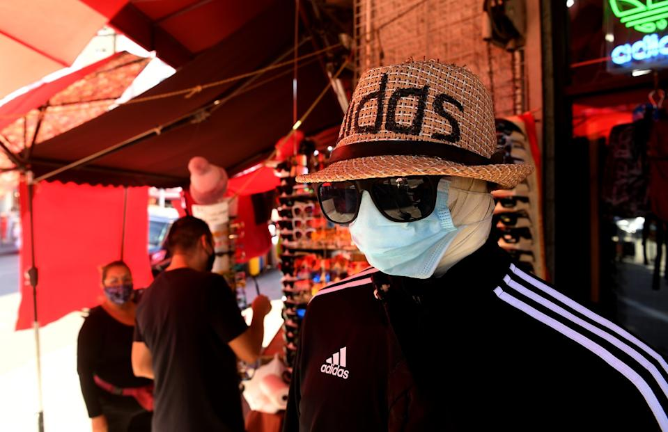 Customers shop along Maple Avenue in Los Angeles near a mannequin in a mask, hat, track jacket and sunglasses.