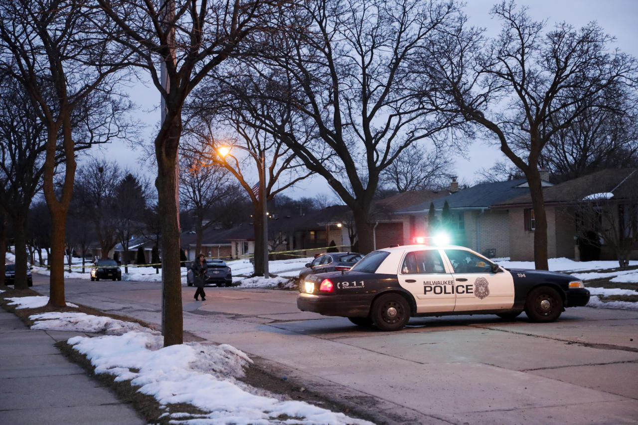 FILE - In the Feb. 26, 2020, file photo, police are seen outside of a house near Potomac and Courtland after a shooting at Molson Coors, in Milwaukee. When a local newspaper reported the identity of the gunman in Milwaukee's mass shooting, it came many hours after that news was broken on Twitter by a self-employed and formerly imprisoned journalist working from his bedroom in California. (AP Photo/Morry Gash, File)