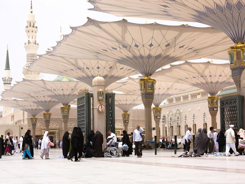 Muslim pilgrims walk in the courtyard of Masjid al-Nabawi ( Prophet's Mosque ): Getty Images