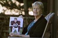 Donna Houston holds up a photograph of her husband, Jim, during his playing years with the Cleveland Browns, Friday, April 3, 2020, in Sagamore Hills, Ohio. Houston's widow would keep notes on her husband's deteriorating condition in a three-ring binder so she would be prepared for the day when he needed full-time care. (AP Photo/Tony Dejak)