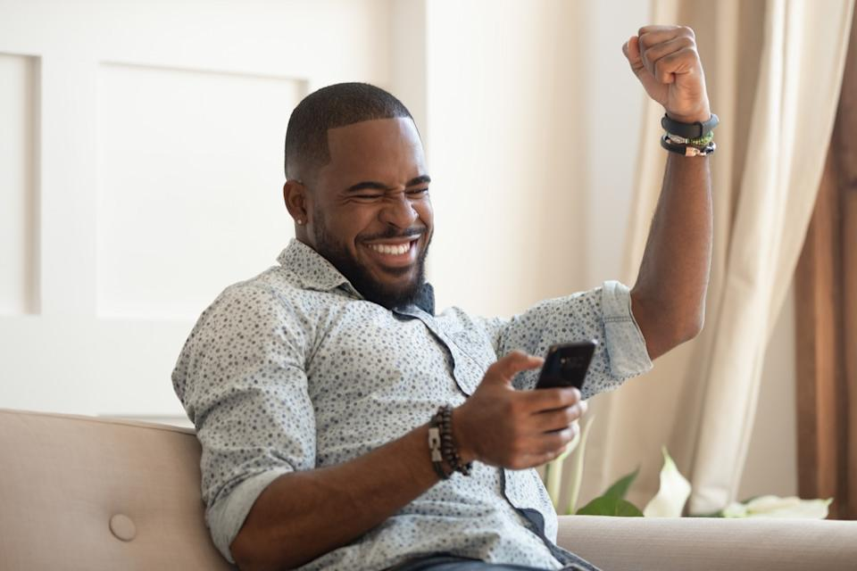 Happy man looking at his phone on the couch cheering