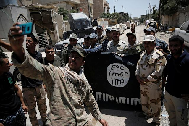 <p>Members of the Iraqi Army's 9th Armoured Division are photographed with an Islamic State flag, claimed after fighting with Islamic State militants in western Mosul, Iraq, June 17, 2017. (Photo: Alkis Konstantinidis/Reuters) </p>