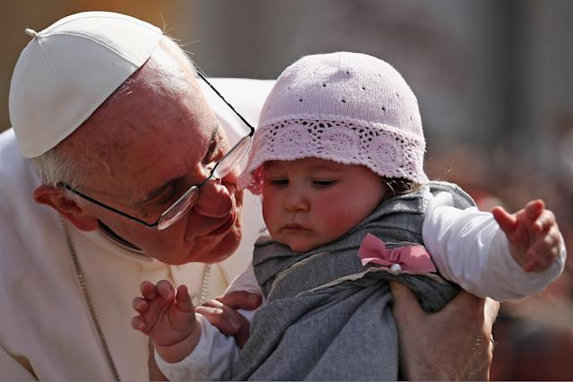 VATICAN CITY, VATICAN - MARCH 24: Pope Francis kisses 8-month-old Victoria Maria Marino from Sicily after delivering his blessing to the palms and to the faithful gathered in St. Peter's Square during Palm Sunday Mass on March 24, 2013 in Vatican City, Vatican. Pope Francis lead his first mass of Holy Week as pontiff by celebrating Palm Sunday in front of thousands of faithful and clergy. The pope's first holy week will also incorporate him washing the feet of prisoners in a youth detention centre in Rome next Thursday, 28th March. (Photo by Dan Kitwood/Getty Images)