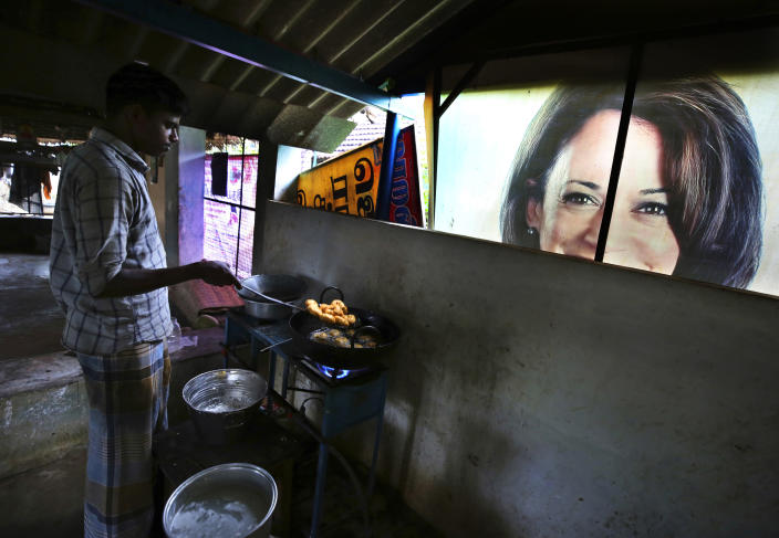 A worker prepares a traditional snack next to a banner featuring U.S. Vice President-elect Kamala Harris, lying outside a local eatery in Thulasendrapuram, the hometown of Harris' maternal grandfather, south of Chennai, Tamil Nadu state, India, Wednesday, Jan. 20, 2021. A tiny village in a remote part of South India is gearing up for celebrations ahead of Kamala Harris' inauguration as the first female vice president of the United States. (AP Photo/Aijaz Rahi)