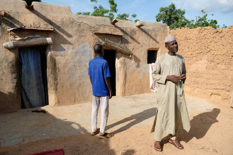 A former student of an Islamic rehabilitation centre, stands with an uncle in his home's courtyard in the town of Daura