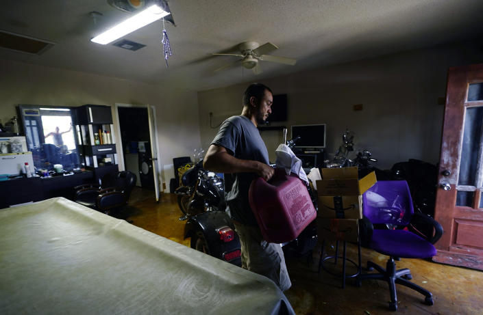 In the wake of Hurricane Ida, Donnie Pearson moves a container of gas at his home after power was restored to his neighborhood, Wednesday, Sept. 1, 2021, in New Orleans, La. Most of New Orleans remains with power. (AP Photo/Eric Gay)