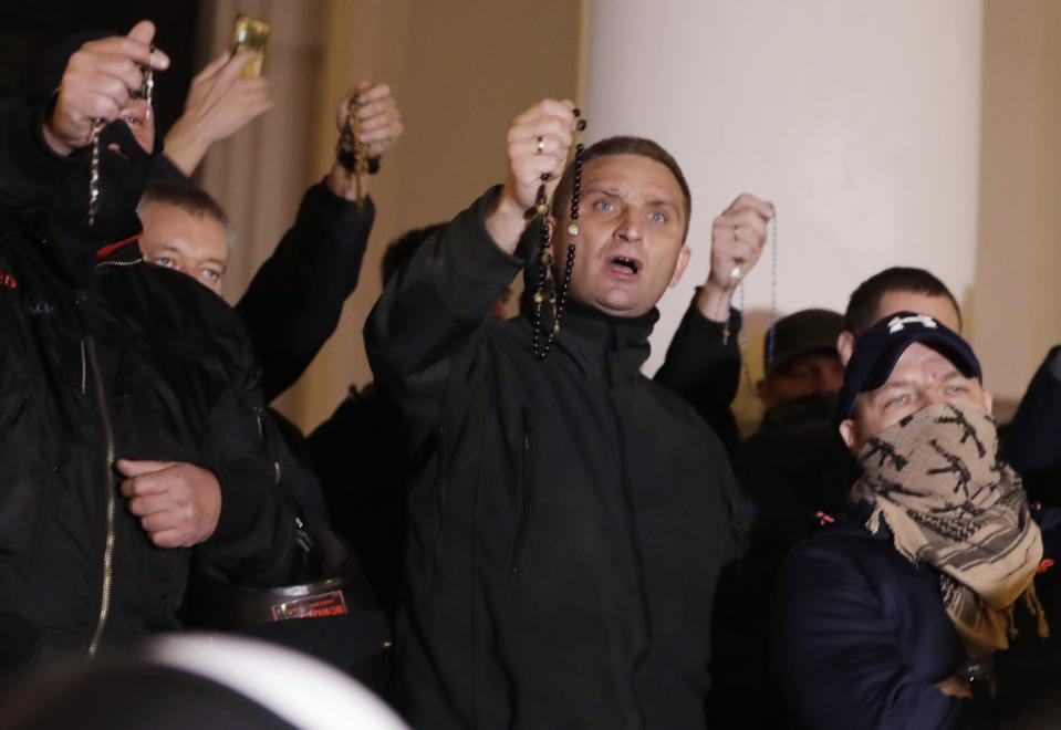 Far-right activists with rosaries sing a religious song as they block entry to a church against hundreds of women's activists and their supporters protesting for the fifth day against a court ruling tightening Poland's strict abortion law, in Warsaw, Poland, on Monday, Oct. 26, 2020. The court said it was unconstitutional to terminate a pregnancy due to fetal congenital defects, effectively banning almost all abortions. (AP Photo/Czarek Sokolowski)