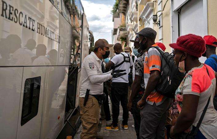Haitian migrants speak with an agent of the National Migration Institute (INM) after remaining on a bus for over seven hours as they refused to get out of the vehicle after being detained at a migration checkpoint in Veracruz, Mexico, on September 13, 2021. - More than 200 migrants were detained in the state of Veracruz on their way north, according to figures provided by the National Institute of Migration (INM). (Photo by VICTORIA RAZO / AFP) (Photo by VICTORIA RAZO/AFP via Getty Images) ORG XMIT: 0 ORIG FILE ID: AFP_9MT4DH.jpg