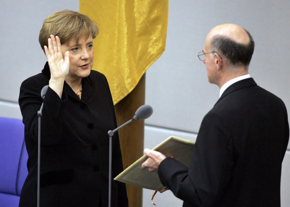 FILE - In this Tuesday, Nov. 22, 2005 file photo, newly appointed German chancellor Angela Merkel, left, takes the oath of office in the parliament in Berlin. Angela Merkel, Germany's first female chancellor, has been praised by many for her pragmatic leadership in a turbulent world and celebrated by some as a feminist icon. But a look at her track record in fighting gender inequality in 16 years running Germany reveals missed opportunities in promoting women's issues. (AP Photo/Fritz Reiss, File)