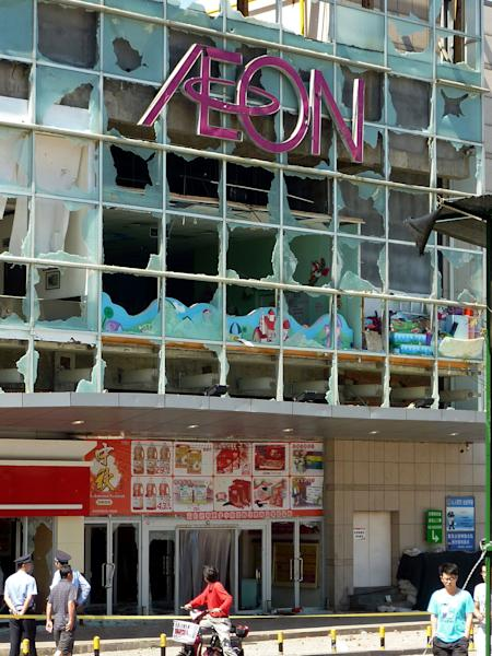 A motorcyclist looks at the damaged facade of an Aeon store in Qingdao, Shandong Province, China, Sunday, Sept. 16, 2012 after demonstrators burst in and destroyed facilities of the Japanese supermarket Saturday. Anti-Japan passions grew more heated this past week in China after Japan's government purchased the contested East China Sea islands - called Diaoyu in China and Senkaku in Japan - from their private Japanese owners. (AP Photo/Kyodo News) JAPAN OUT, MANDATORY CREDIT, NO LICENSING IN CHINA, HONG KONG, JAPAN, SOUTH KOREA AND FRANCE