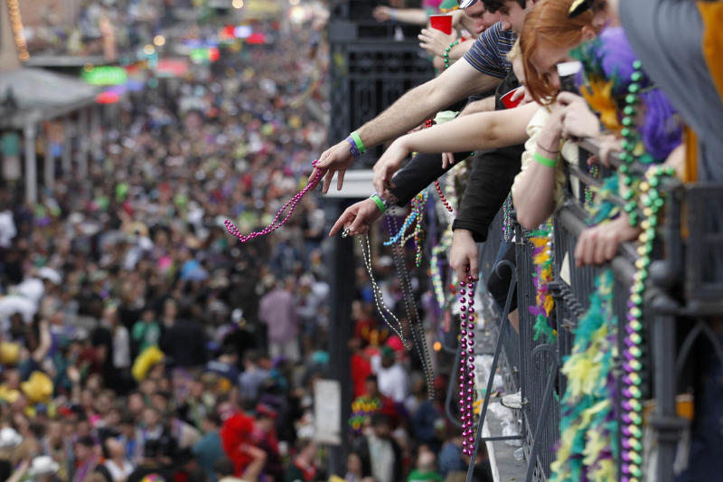"""FILE - In this March 8, 2011 file photo, revelers throw beads from the balcony of the Royal Sonesta Hotel onto crowds on Bourbon Street during Mardi Gras Day festivities in the French Quarter in New Orleans. Mardi Gras is Tuesday, Feb. 12, 2013, but more than a dozen parades roll in the days leading up to Fat Tuesday. The Krewe of Endymion's """"super float"""" rolls Saturday night in New Orleans led by pop star Kelly Clarkson. Sunday's Bacchus parade will include more than two dozen child cancer patients from hospitals across the country who will ride with Bacchus celebrity king, actor G.W. Bailey. On Monday, actor Gary Sinise and New Orleans musicians Troy """"Trombone Shorty"""" Andrews and Harry Connick Jr. will ride in the Krewe of Orpheus parade. (AP Photo/Gerald Herbert, file)"""