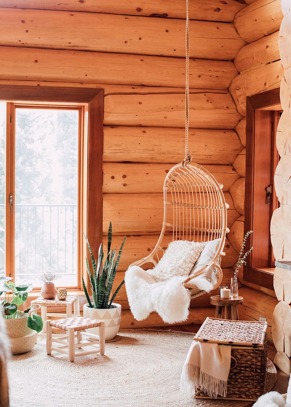"""This cozy corner is just one of the many spaces where every detail is, in fact, in its rightful, styled place. """"When looking at the space in detail, it felt only natural to offset the dark, heavy wood grains with something fresher and lighter to really encourage the play on natural light,"""" Kula explains. The textured sheepskin rugs, the woven stools, the hanging rattan chair, and the greenery playfully contrast yet perfectly complement the log wall interior of the cabin."""