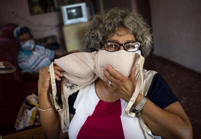 Idania Espanola, 63, poses for a photo showing a bra that she will adapt into two face masks, amid the spread of the new coronavirus in Cojimar, Cuba, east of Havana, Tuesday, March 31, 2020. (AP Photo/Ramon Espinosa)