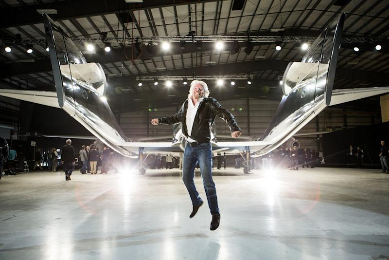 Sir Richard Branson leaping for joy in front of WhiteKnightTwo mothership